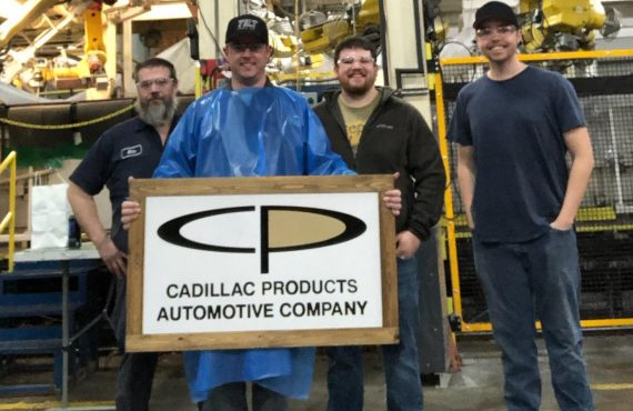 Cadillac Product Manufacturing Workers holding logo sign